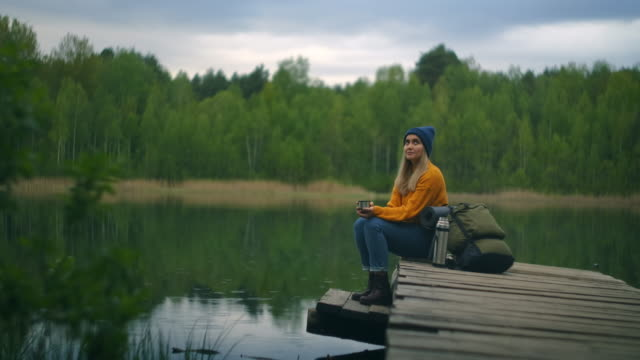A female traveler drinks tea with a backpack and enjoys the beauty of a mountain forest lake sitting on a wooden pier. Slow-motion concept of a lonely woman's solitary journey. Quarantine and travel