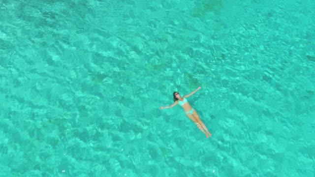 top down: female traveler enjoying her vacation in the glassy ocean water. - ritemprarsi video stock e b–roll