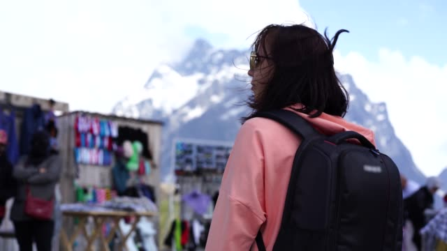 Female traveler on market in mountainous terrain. Woman tourist considering souvenirs in shopping booths Woman tourist considering souvenirs in shopping booths. souvenir stock videos & royalty-free footage