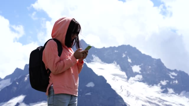 Female traveler stands with smartphone in mountains. Woman tourist browsing mobile phone against cloudy sky on sunny day in mountainous terrain