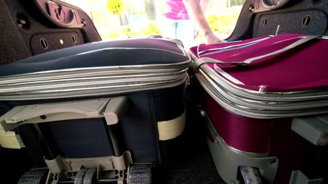 vidéos et rushes de voyageur femmes prenant les valises dans le coffre de voiture - wagon