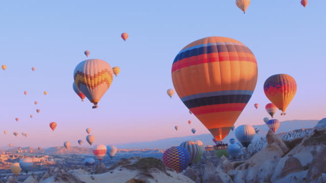 Video Female traveler with backpack looking to the air baloons. sporty girl and a lot of hot air balloons. The feeling of complete freedom, achievement, achievement, happiness