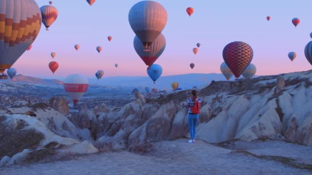 vídeos y material grabado en eventos de stock de mujer viajera con mochila mirando a los baloons de aire. chica deportiva y un montón de globos aerostáticos. la sensación de libertad completa, logro, logro, felicidad - experience