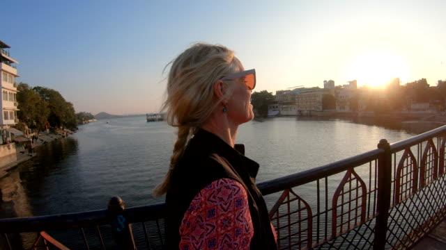 vídeos de stock e filmes b-roll de pov of female traveller walking across bridge at sunrise - 55 59 anos