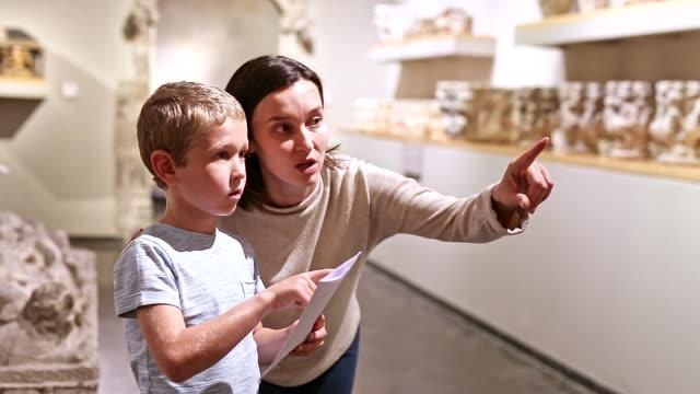 vrouwelijke leraar met jongen die expositie in museum bekijkt video