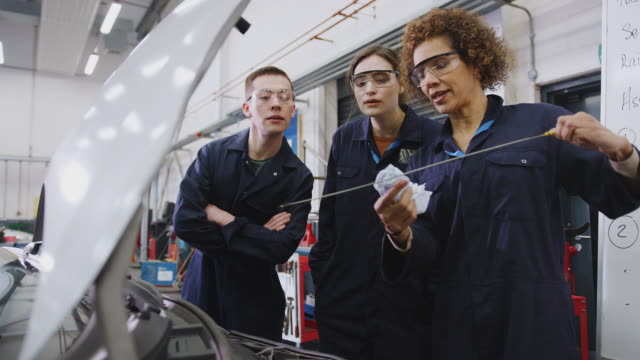 Female Tutor With Students Checking Oil Level In Car Engine On Auto Mechanic Course At College