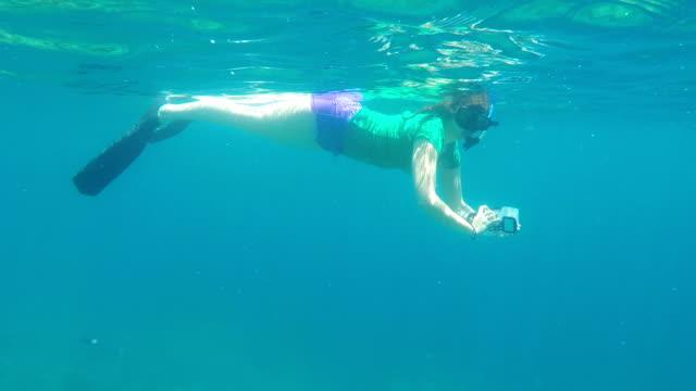 Female underwater swimmer snorkeling in North Bali coral reef video