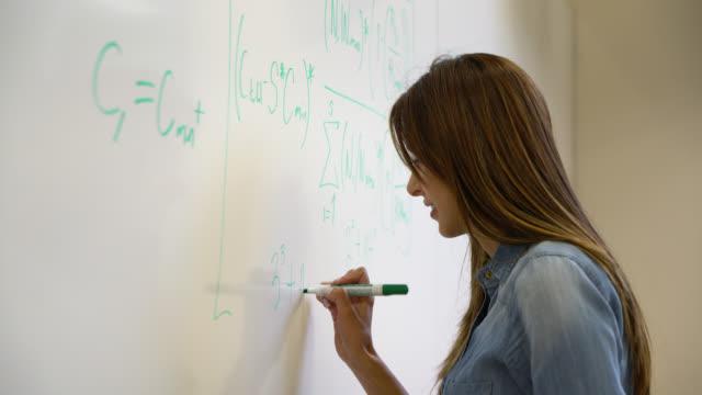 studentka uniwersytetu pisząca formułę na planszy z filcowym markerem końcówki - symbol matematyczny filmów i materiałów b-roll