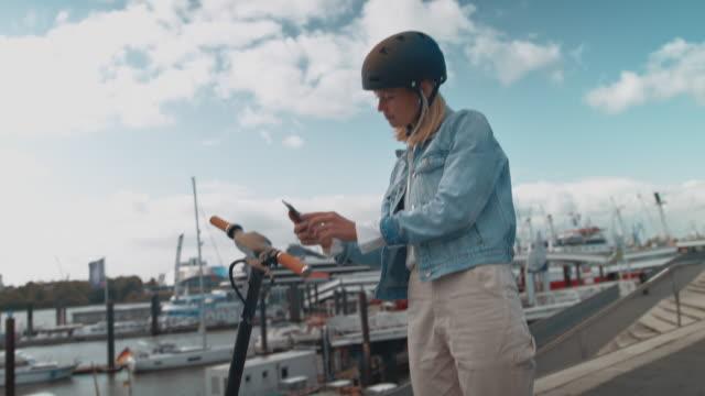 female unlocking electric scooter with cellphone - monopattino elettrico video stock e b–roll