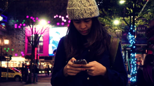 Female using smart phone in city at night video