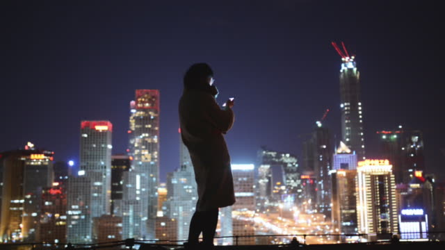 Female using smartphone in city at night Female using smartphone in city at night chance stock videos & royalty-free footage