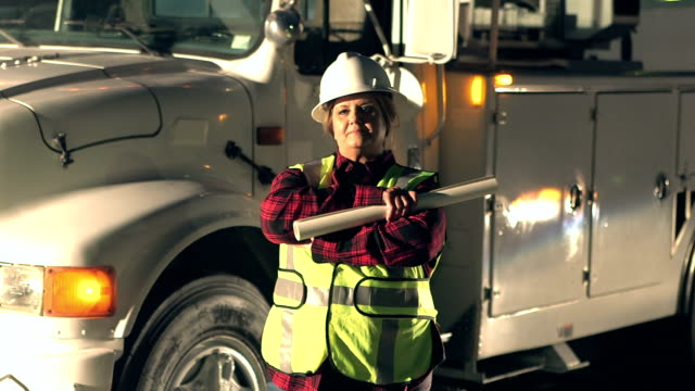 Female utility worker standing by truck - video