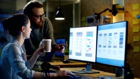 vidéos et rushes de ux femelle architecte consulte ingénieur d'études, ils travaillent sur des applications mobiles tard dans la nuit, elle boit du café. ils sont a l'air très créatif et cool. - bureau ameublement