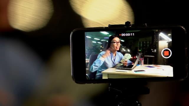 여성 비디오 블로거 보여주는 카메라 달러 현금 공짜 비디오 녹화 - influencer 스톡 비디오 및 b-롤 화면