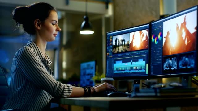 女性のビデオ編集の映像とパソコンは音の取り扱い彼女のオフィスは現代および創造的なロフト スタジオです。 - 編集者点の映像素材/bロール