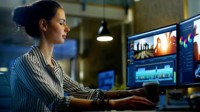 女性のビデオ編集の映像とパソコンは音の取り扱い彼女は遅くまで仕事をし、コーヒーを飲みます。彼女のオフィスは現代および創造的なロフト スタジオです。 - 編集者点の映像素材/bロール