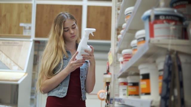 weibliche besucher des shops ist flasche aus regal nehmen und lesen in halle mit farbstoffen - etikett stock-videos und b-roll-filmmaterial