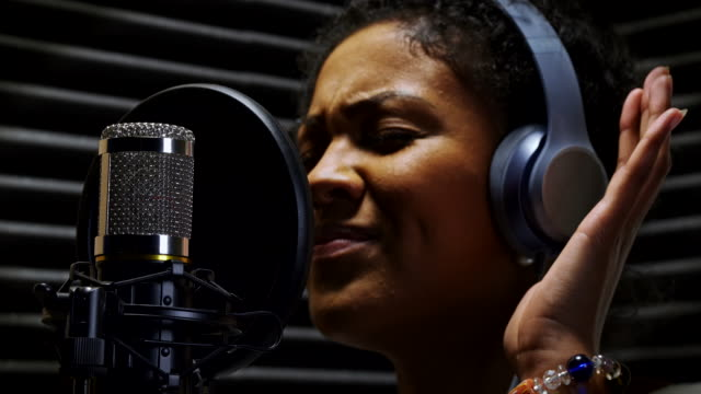 female vocalist wearing headphones singing into microphone in recording studio - musicians singers during lockdown video stock e b–roll