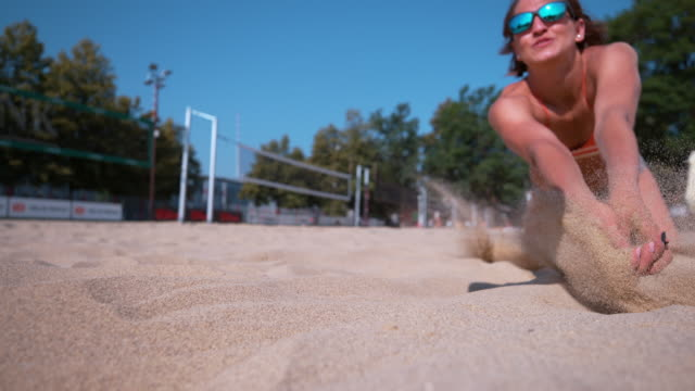 CLOSE UP, DOF: Female volleyball athlete dives for a point during a tournament. SLOW MOTION, CLOSE UP, DOF: Female volleyball athlete dives for a point during a summer tournament. Fit Caucasian girl playing beach volleyball crashes into the hot sand while trying to reach the ball volleyball sport stock videos & royalty-free footage