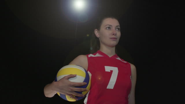 Female volleyball Player Portrait pose - Super Slow Motion 180 degree rotation Stock HD video clip footage of a female volleyball Player. Filmed in Super Slow motion, the camera rotates 180 degrees around the player. Black Background. Indoors pre game stock videos & royalty-free footage
