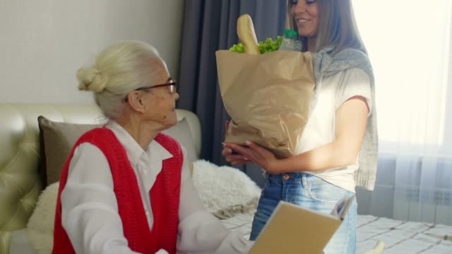 female volunteer bringing groceries to senior woman - grocery home video stock e b–roll
