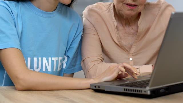 kvinnlig volontär visar åldern lady laptop programvara, planering besök till läkare - stavning bildbanksvideor och videomaterial från bakom kulisserna