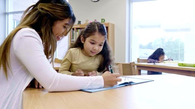 Female volunteer tutor helps young schoolgirl with assignment