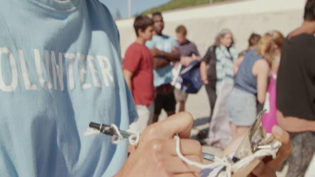 vidéos et rushes de femme écrivant sur le presse-papiers à la plage 4k - bloc note