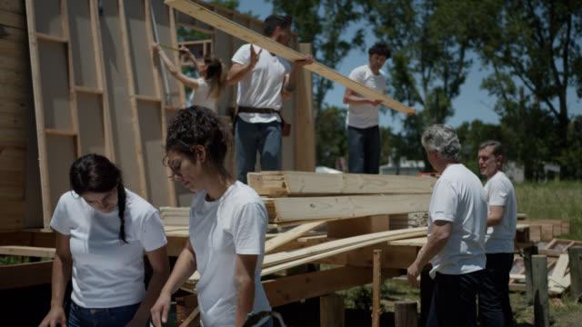 vídeos de stock, filmes e b-roll de voluntárias do sexo feminino verificando o projeto de um projeto habitacional enquanto a equipe está trabalhando em segundo plano - voluntário