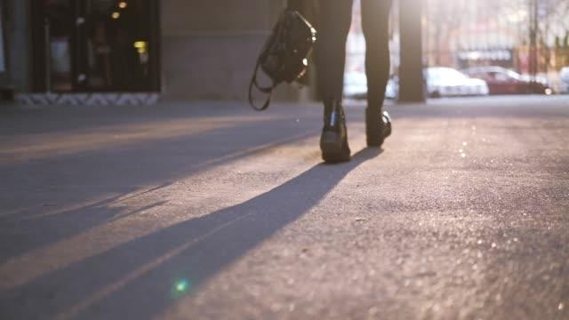 kadın yürüyüş sokak kırmızı tartan etek botlar - uzun adımlarla yürümek stok videoları ve detay görüntü çekimi