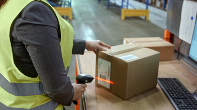 Female warehouse employee scanning packages on a desk in the warehouse with a handheld scanner video