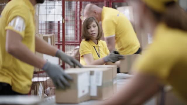 ld 女性倉庫員工採取包從傳送帶和堆疊在一起 - postal worker 個影片檔及 b 捲影像