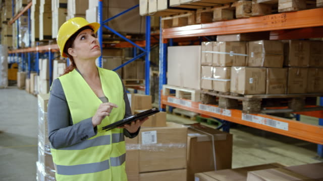 Female warehouse supervisor working on a tablet while standing next to a full pallet in the warehouse video