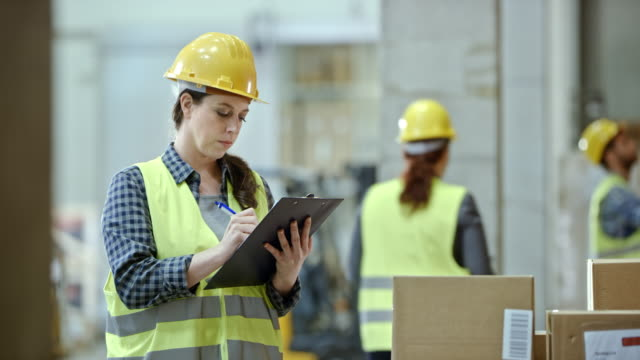 Female warehouse supervisor writing on a clipboard while standing in the warehouse video