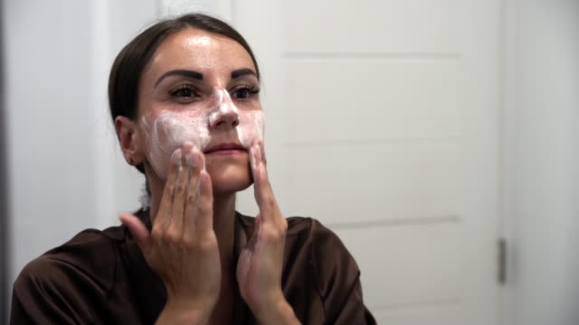 female washes, rubs, smears with cream, face with acne - disintossicazione video stock e b–roll
