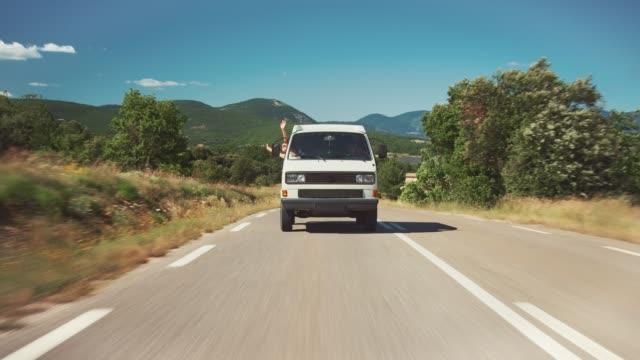 female waving hands from van window during trip - furgone video stock e b–roll