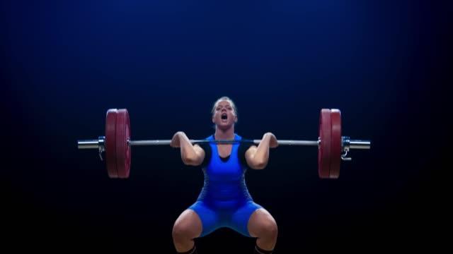競争でクリーンでジャークリフトを行うブルーの衣装で女性の重量挙げ - 持ち上げる点の映像素材/bロール
