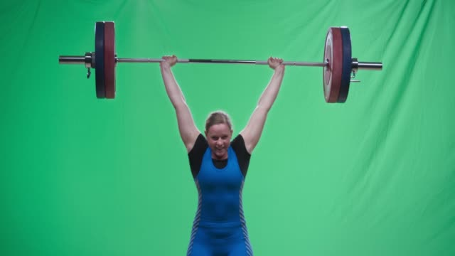 Female weightlifter in blue outfit performing the clean and jerk lift