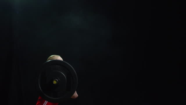Female Weightlifter Lifting Barbell on Black Background