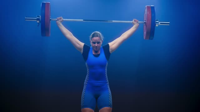 Female weightlifter lifting the barbell at a competition performing the snatch lift