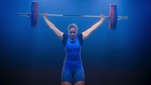 тяжелоатлетка, поднимающая штангу на соревновании, выполняя рывок - вес стоковые видео и кадры b-roll