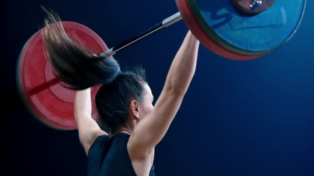 SLO MO TU Female weightlifter performing a snatch lift at a competition
