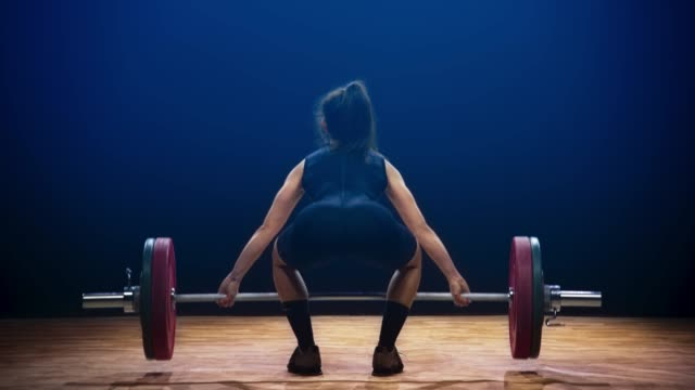 Female weightlifter performing the snatch lift at a competition