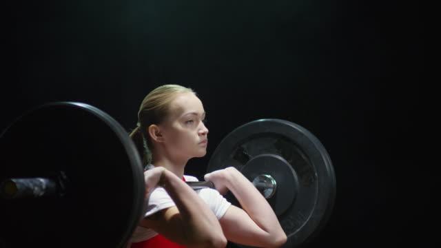黒の背景にバーベルを持ち上げる女性の重量挙げ - ウエイトトレーニング点の映像素材/bロール