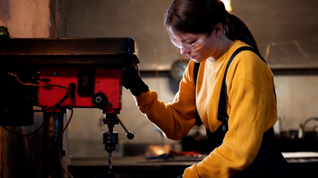 Female welder drill a metal There are two woman and one man, they are in their shop, working together. metal worker stock videos & royalty-free footage