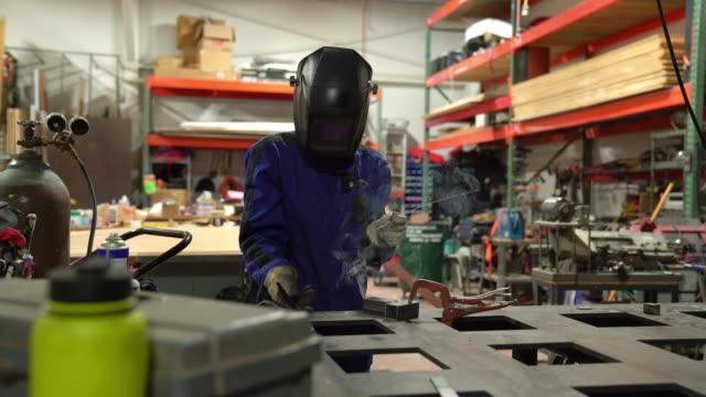 Female welder preparing to work in her workshop video