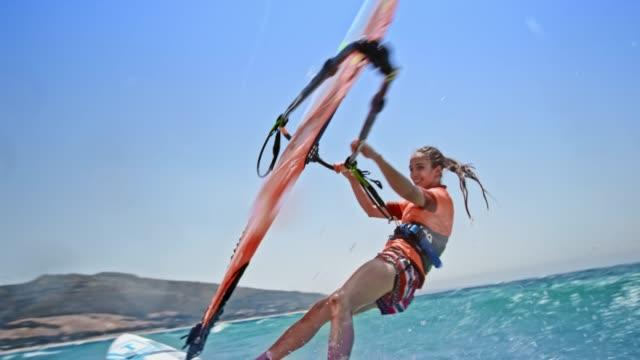 vídeos de stock, filmes e b-roll de slo mo feminino windsurfista sorrindo enquanto andar na luz do sol - férias na praia