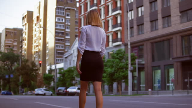 female with blond hair walks on the street - ludzka osada filmów i materiałów b-roll