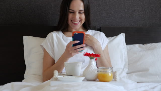 Female with phone sitting with service tray in bed video