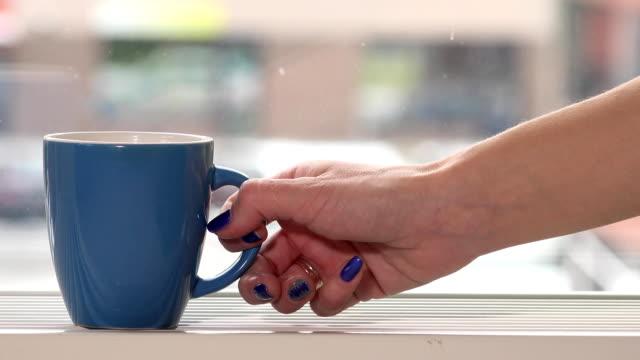 stockvideo's en b-roll-footage met vrouwelijke vrouw hand nemen cup met hete thee koffie drinken en sneeuwvlokken buiten - camelia white
